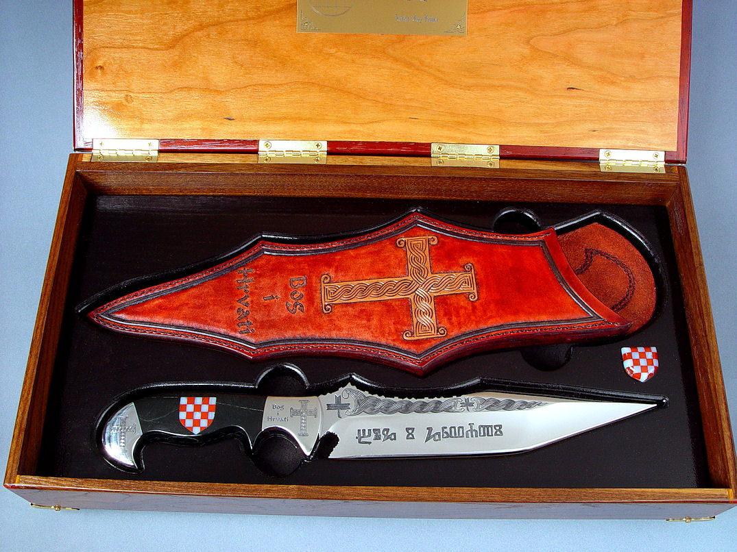 """Duhovni Ratnik"" Knife in hand-engraved 440C high chromium stainless steel blade, hand-engraved 304 stainless steel bolsters, handle of Black Nephrite Jade gemstone inlaid with a mosaic of Red River Jasper and White Geodic Quartz. Sheath is hand-carved, hand-dyed leather shoulder"