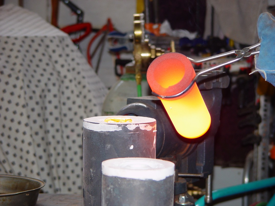 Pouring Molten silicon bronze into molds at 1975 degrees F for sword guard casting at Enchanted Spirits Studio