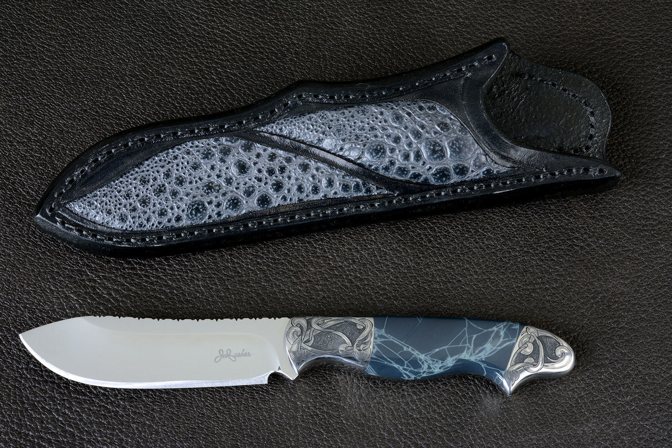 """Regulus"" obverse side view in 440C high chromium stainless steel blade, hand-engraved 304 stainless steel bolsters, Spiderweb Obsidian gemstone  handle, Frog skin inlaid in hand-carved leather sheath"