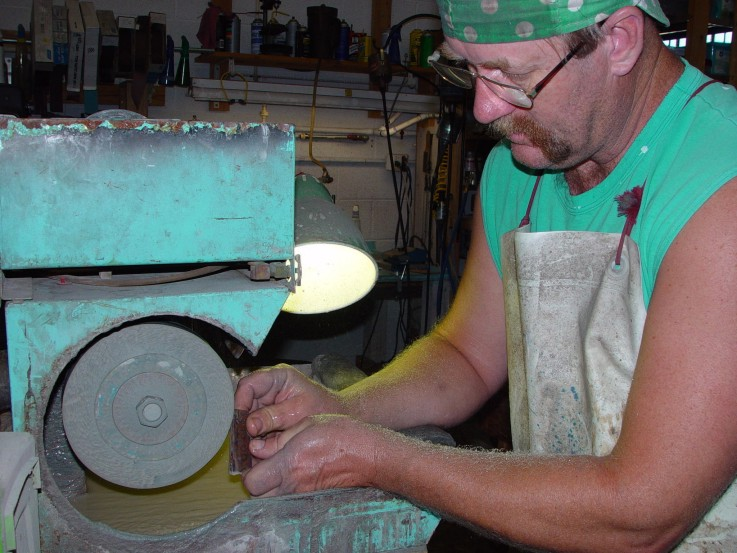 Roughing in gemstone handle material on the lapidary wet grinder