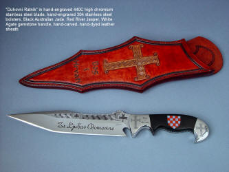 """Duhovni Ratnik"" obverse side view. Knife in hand-engraved 440C high chromium stainless steel blade, hand-engraved 304 stainless steel bolsters, handle of Black Nephrite Jade gemstone inlaid with a mosaic of Red River Jasper and White Geodic Quartz. Sheath is hand-carved, hand-dyed leather shoulder"