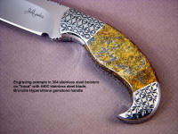 Iraca: fine handmade knife by Jay Fisher, obverse side view: 440C high chromium stainless steel blade, hand-engraved 304 stainless steel bolsters, Bronzite Hypersthene gemstone handle, Frog skin inlaid in hand-carved leather sheath