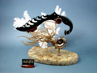 """Aegir"" knife sculpture in mirror polished, hot blued O1 high carbon tungsten-vanadium alloy tool steel blade, blued steel bolsters, 14kt gold bezels, peridot gemstones, Nebula stone gemstone handle, stand of cast bronze, white Carribean coral, Venetian gold granite with garnets"