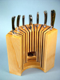 """Chef's Set"" knives in block view. Nice radial design of block compliments the nested bowls at the base. All handles are similarly shaped and contoured."
