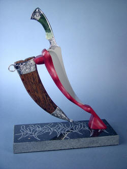 """Desert Wind"" side view on stand. Note graceful lines, matching at the sheath angle and blade angle."