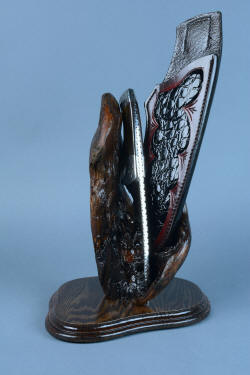"""Golden Eagle"" custom knife, in stand view, spine forward. Full filework stands out against the dark burl wood"