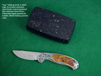 """Izar"" linerlock folding knife, obverse side view in 440C high chromium stainless steel blade, hand-engraved 304 stainless steel liners, 6AL4V anodized titanium lockplate, Pietersite Agate gemstone handle, Black Galaxy Granite gemstone case lined with leather"