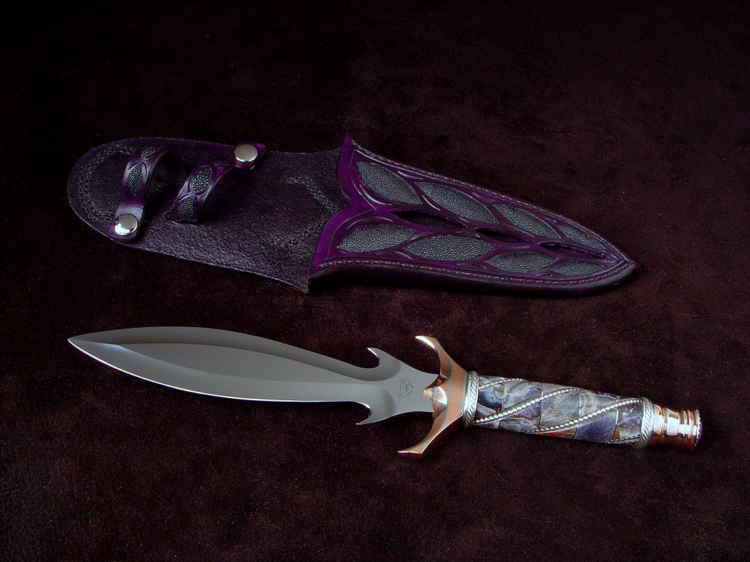 """Amethistine"" dagger, obverse side view in 440C high chromium stainless steel blade, diffusion welded copper, nickel silver fittings, sterling silver gallery wire wrap and accents, Amethyst crystal gemstone pommel, hand-carved leather sheath inlaid with black rayskin"