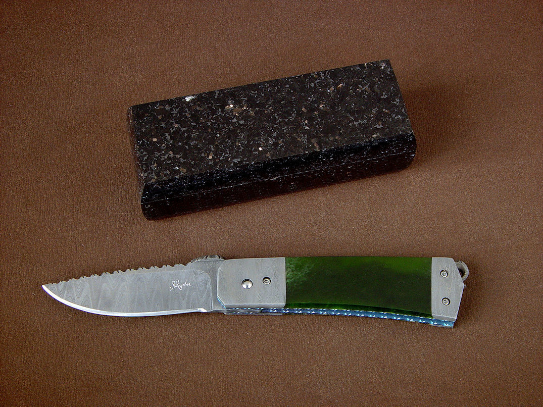 """Aries"" folding knife, obverse side view in damascus stainless steel blade and bolsters, anodized titanium liners, New Zealand Jade gemstone handle, Black Galaxy Granite gemstone case"