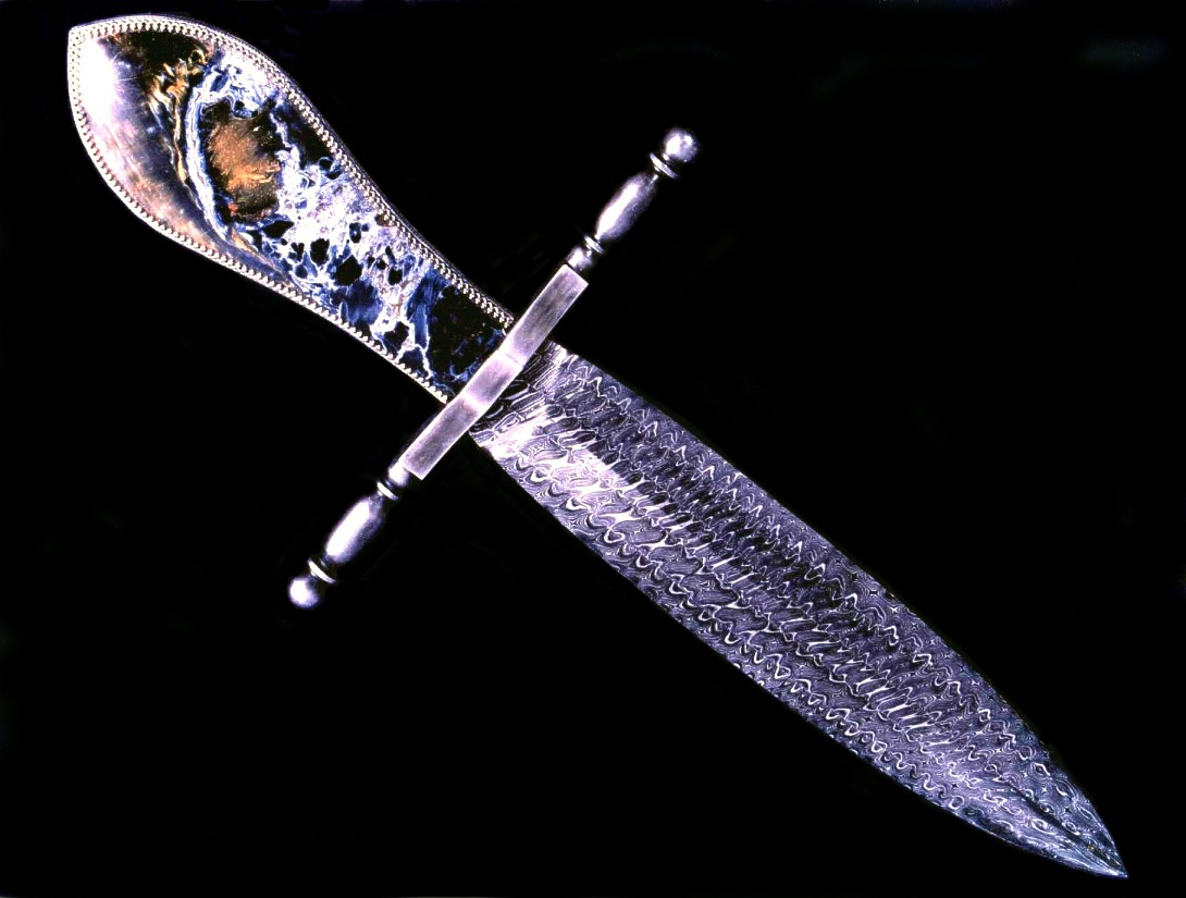 """Conquistador"" dagger in twist carbon steel damascus pattern welded blade, antiqued blued steel crossguard, sterling silver bezels and Pietersite Agate gemstone handle"