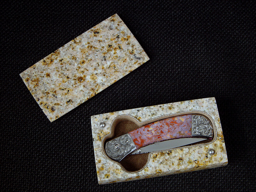 """Gemini"" fine custom handmade knife in granite case. Knife is 440C high chromium stainless steel blade, hand-engraved 304 stainless steel bolsters, Confetti agate gemstone handle scales, anodized 6AL4V titanium liners"