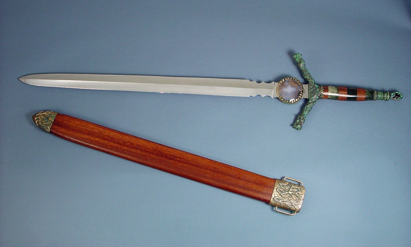"""Lycaon"" handmade custom broadsword, mounted view  in 440C high chromium stainless steel blade, cast bronze fittings, guayabillo hardwood and nephrite jade gemstone handle, obsidian pommel, lauan hardwood scabbard with cast bronze chape, display board of ebonized red oak, steel, black suede, American Black Walnut, engraved black lacquered brass"