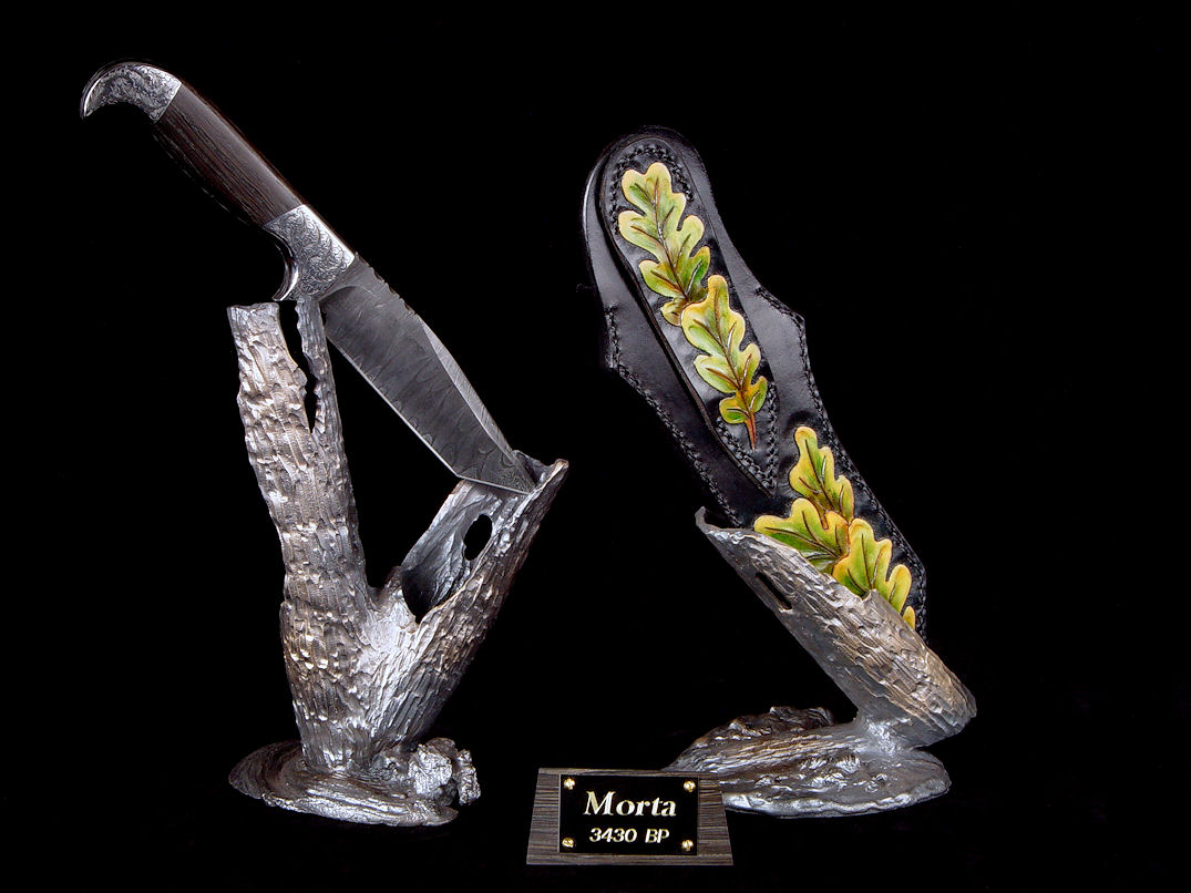 """Morta"" reverse side view in twist damascus pattern welded steel blade, hand-engraved 304 stainless steel bolsters, Bog Oak mineralized hardwood handle, sheath of hand-carved leather shoulder, hand-dyed, stand of hand-cast bronze"