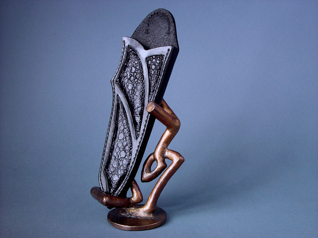 "Sheath and stand for ""Tharsis Intense."" Sheath is hand-carved leather shoulder inlaid with frog skin, resting on hand-cast bronze stand"