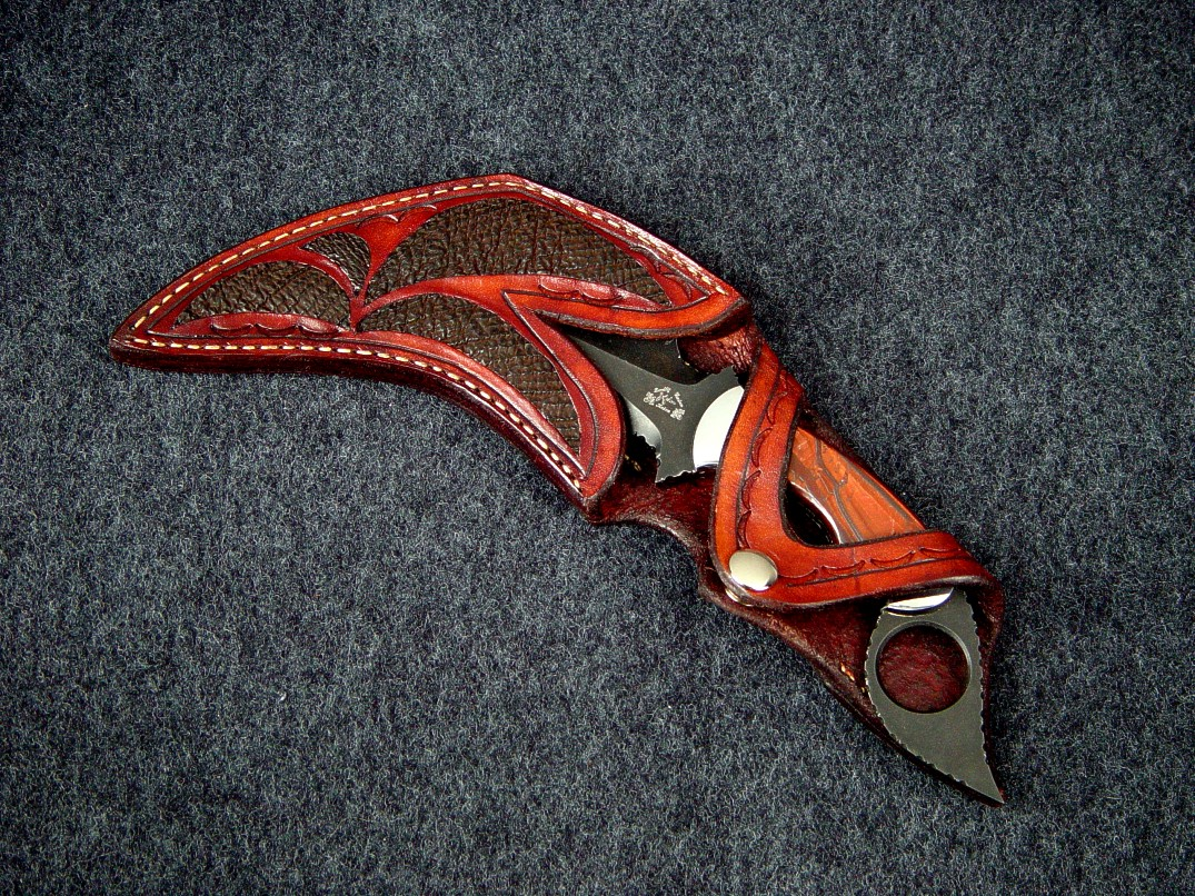 """Triton"" double edged kerambit with open handle display type sheath. Knife is blued O-1 tool steel, stainless steel bolsters, Red Tiger eye gemstone handle. Sheath has Cape Buffalo skin inlays"