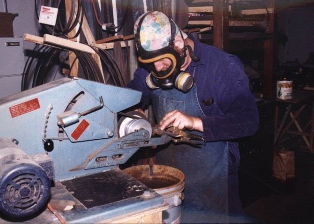 Jay Fisher, working at the belt grinder, profiling blades with a fiberglass reinforced cutoff wheel at 5000 sfpm.