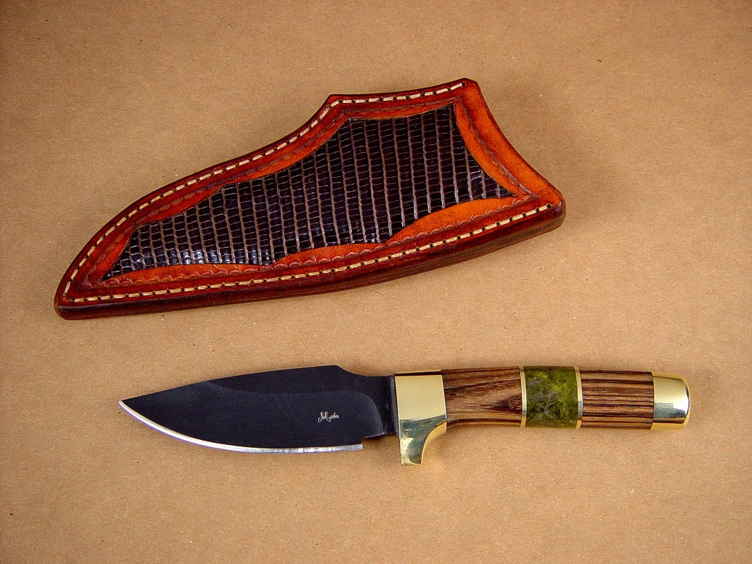 "Fine custom handmade knives: ""Alamogordo"" Obverse side view: O-1 high carbon tungsten-vanadium alloy tool steel blade, bead blasted and hot blued, brass guard, pommel, and fittings, zebrawood hardwood and serpentine gemstone handle, lizard skin inlaid in hand-carved leather sheath"