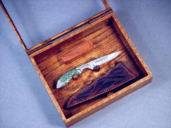 """Durango"" open display case detail. Knife and sheath are lightly wedged in holders of Lauan hardwood"