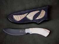 """El Tanin"" obverse side view in mirror polished, hot blued O1 high carbon tungsten-vanadium tool steel blade, 304 stainless steel bolsters, White Petrified Wood gemstone handle, Cobra skin inlaid in hand-carved leather sheath"