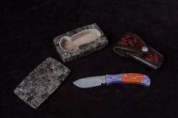 """Elysium"" ensemble including fine handmade liner lock folding knife with gemstone handle and titanium bolsters and liners, hand-carved sheath inlaid with red rayskin, knife sarcophagus in polished anorthosite gemstone"