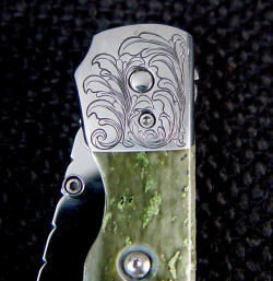 """Gemini"" linerlock folding knife engraved bolster detail, obverse side"