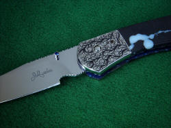 """Gemini"" folding knife, obverse side front bolster engraving detail. Engraving design utilizes orbicular pattern and droplet shape exhibited in the gemstone  handle scales."