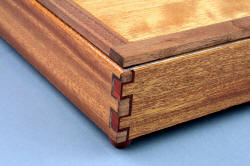 """Kadi"" hardwood case, joinery detail. Double-double box joints in lauan, black walnut, redheart hardwood. Feet are turned redheart hardwood."