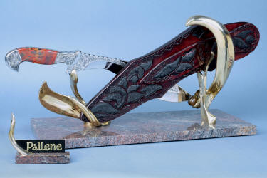 """Pallene"" khukri, obverse side view in CPM154CM High molybdenum powder metal technology stainless tool steel blade, hand engraved, with hand-engraved 304 stainless steel bolsters, Brecciated Jasper gemstone  handle, hand-carved leather sheath inlaid with rayskin, hand-cast silicon bronze and Imbuya hardwood stand and Paradiso Classico Granite base"
