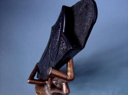 """Tharsis Intense"" sheath downward view on stand. Textures are varied and complex in the leather, skin, and bronze materials"