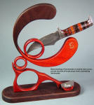 """Omega"" in articulating display stand of bloodwood, walnut hardwood and brass. Knife is carbon damascus steel with petrified wood handle"