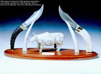 """Rhino Dawn"" stand is hand-carved alabaster, bloodwood, staghorn, knife handles are gazelle horn, wart hog tusk"