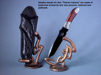 """Tharsis Intense"" in mirror polished and hot blued O1 high carbon tungsten vanadium tool steel blade, hand-engraved 304 stainless steel bolsters, Fossilized Stromatolite Gemstone handle, sheath in leather inlaid with black frogskin, stands of sculpted, hand-cast bronze"
