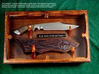 """The Veteran"" in display case of poplar with mahogany hinges, hangers of bloodwood signifying sacrifice. Knife has petrified dinosaur bone gemstone handle, etched stainless steel blade, hand-cared leather sheath"